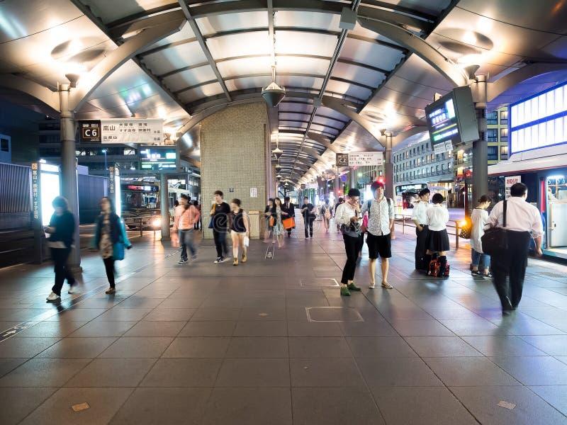 未认出的人民在京都驻地公共汽车总站排队在晚上 免版税库存照片