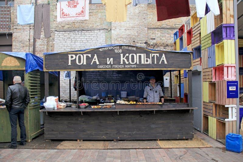 未认出的人民烹调,并且在食物的贸易传统傲德萨盘在街道食物节日失去作用在基辅,乌克兰 免版税库存图片