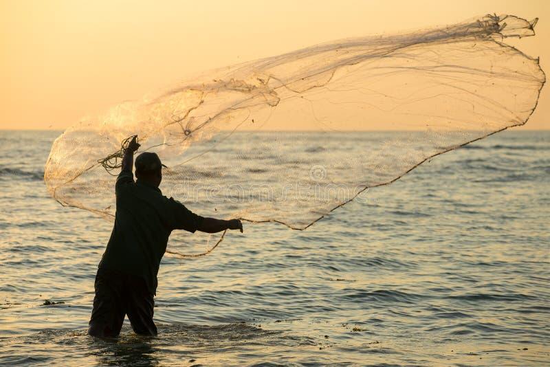 未认出的印地安渔夫投掷的网的剪影在海 免版税库存图片