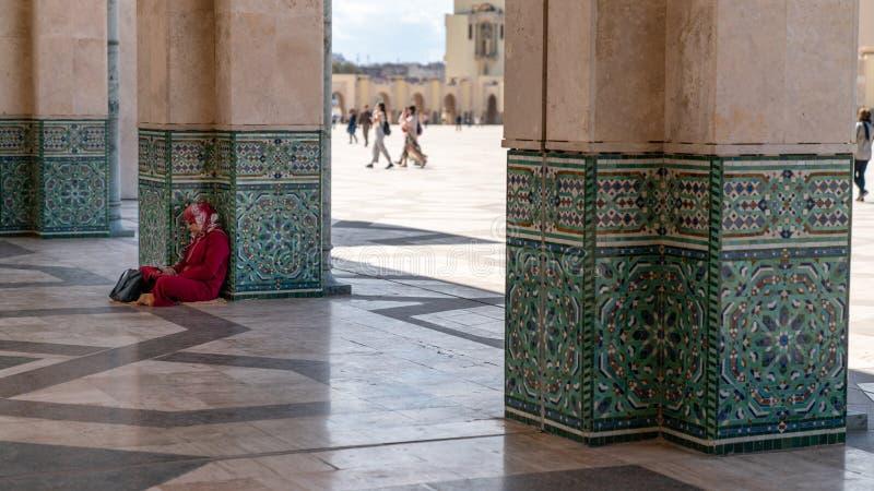 未认出的妇女坐的倾斜对哈桑二世清真寺的专栏在卡萨布兰卡,摩洛哥 免版税库存照片