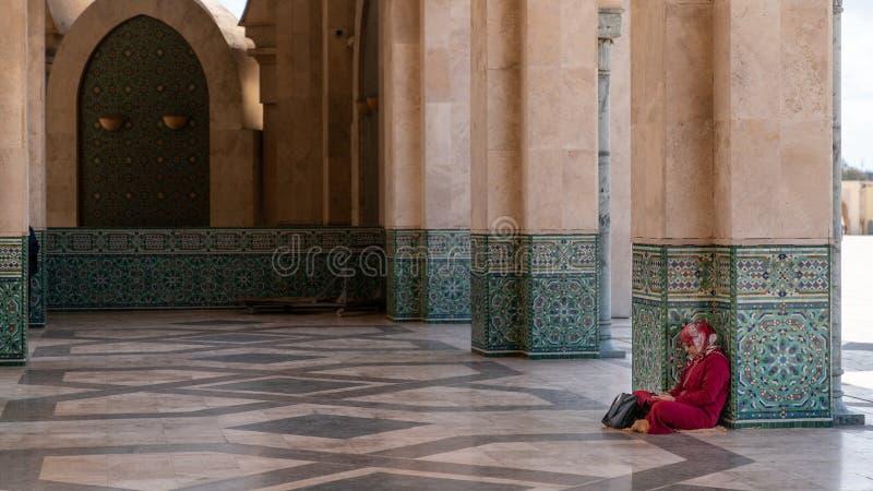未认出的妇女坐的倾斜对哈桑二世清真寺的专栏在卡萨布兰卡,摩洛哥 库存照片