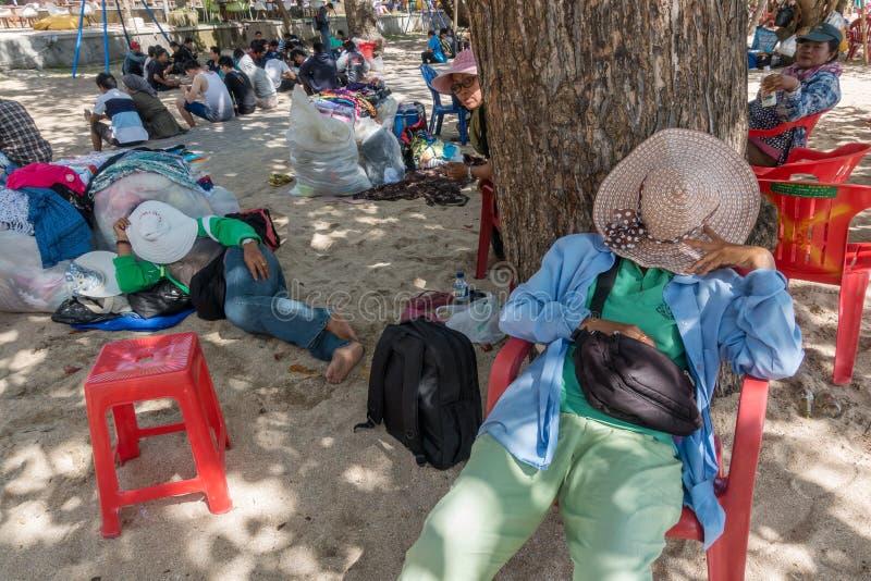 未认出的巴厘语布裙供营商有休息在海滩的阴影 库存图片