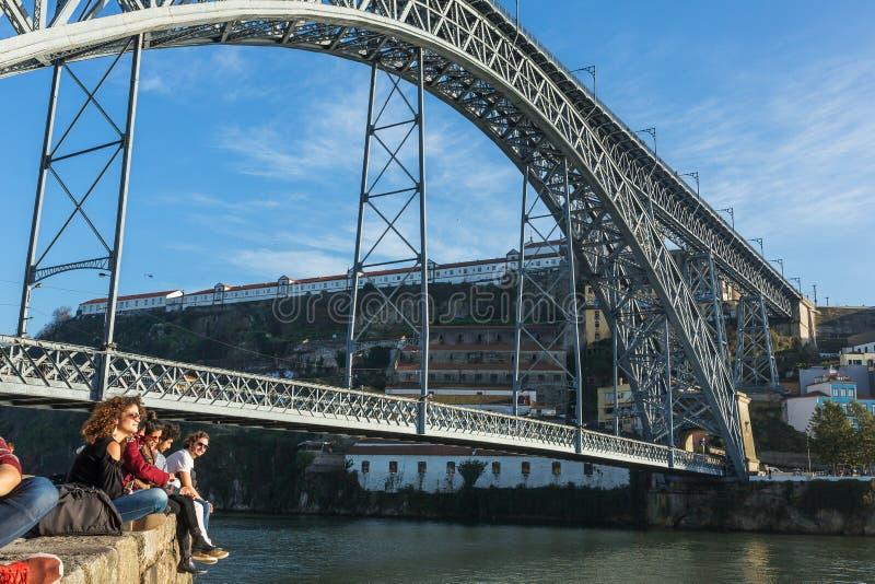 未认出的年轻背包徒步旅行者休息在著名桥梁Ponte dom雷斯下在波尔图,葡萄牙 库存照片