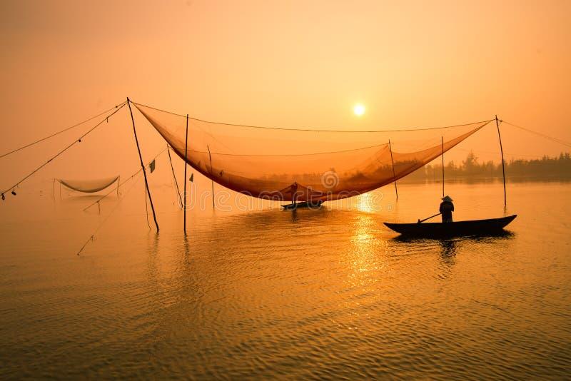 未认出的渔夫在河的清早检查他的网在Hoian,越南 库存图片