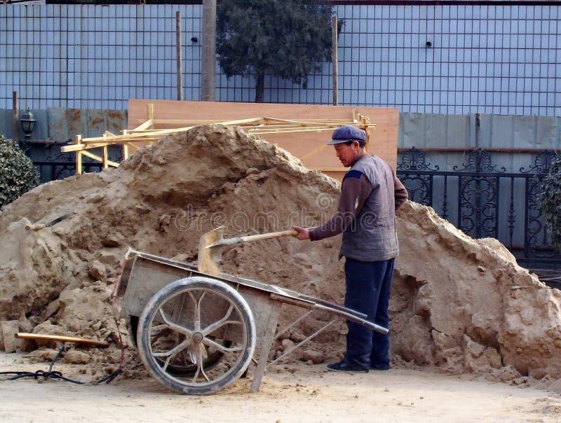 未认出的辛苦铲起的沙子到一辆木独轮车里在唐山,中国 免版税库存照片