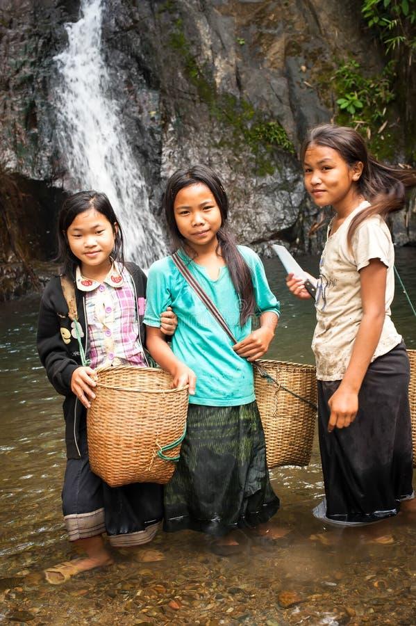 未认出的逗人喜爱的亚裔女孩临近热带瀑布 老挝 免版税图库摄影