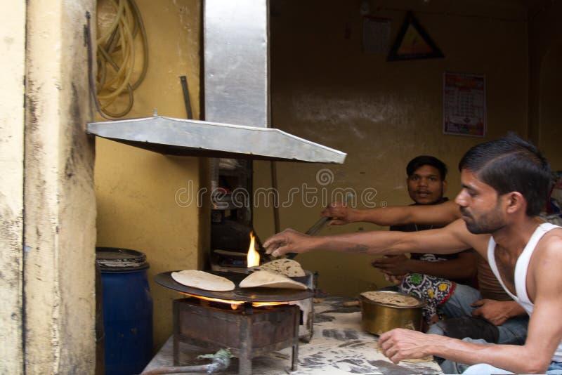 本机的吃饭的客人 传统薄煎饼在被烘烤开火 库存图片