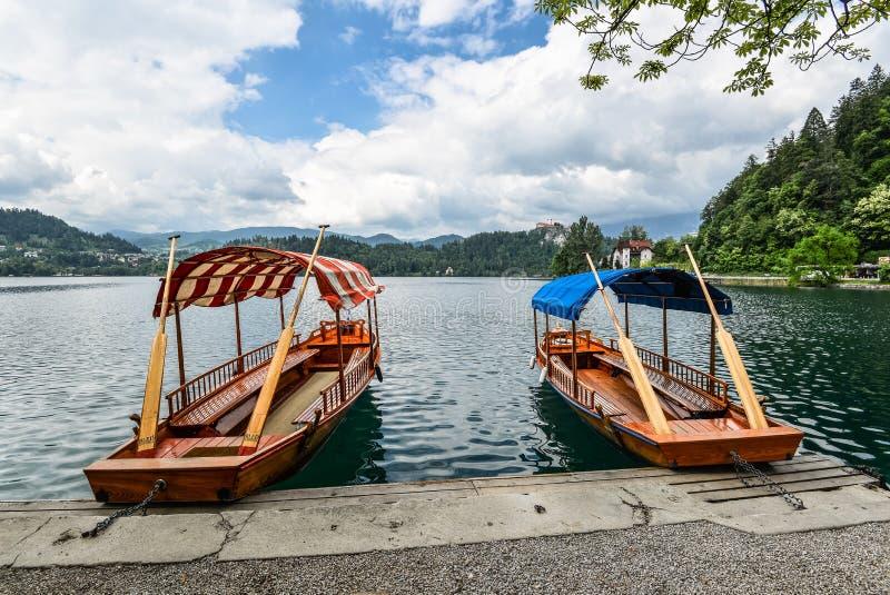 朱利安阿尔卑斯山和两条老木小船的美丽的布莱德湖 免版税库存图片