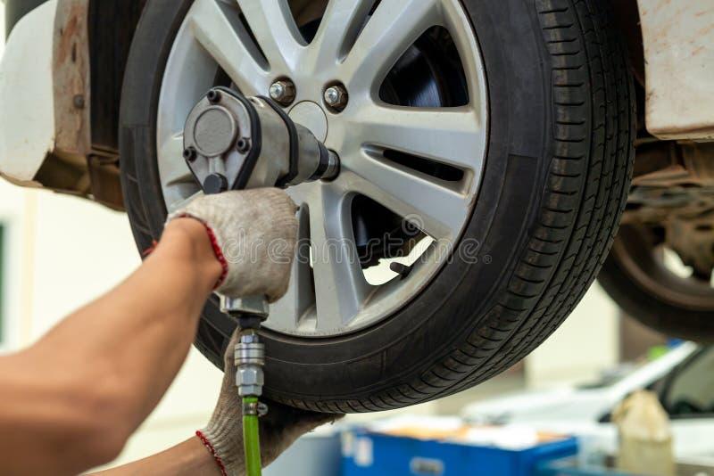 机修工改变的车轮汽车修理店 免版税库存照片