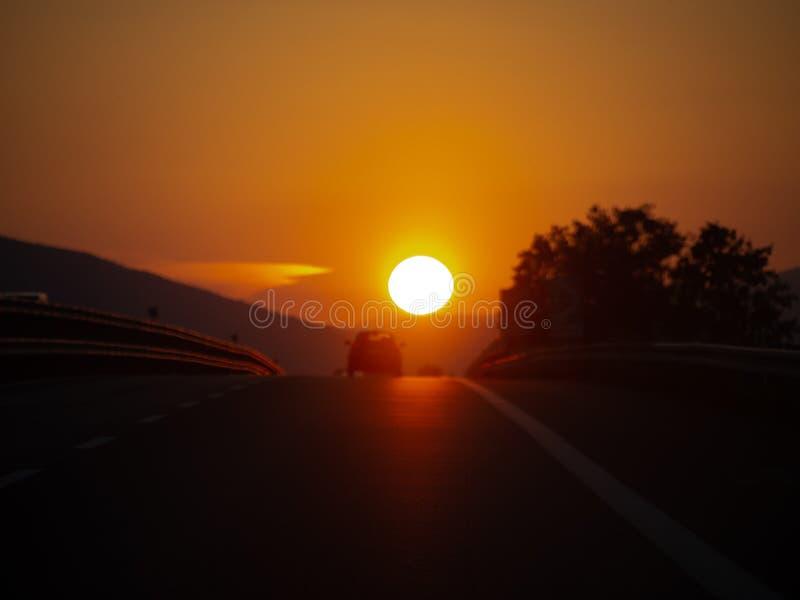 机动车路日落,当假日游客汽车返回从假期,假日 驶回本国的 真正图象 大太阳 免版税库存照片