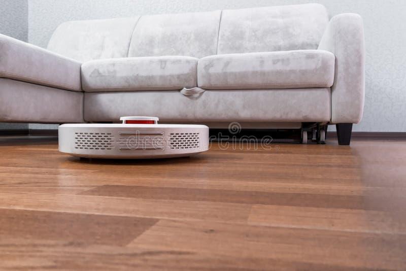 机器人吸尘器在层压制品的地板上的沙发附近跑 声音命令控制的机器人指挥清洁 现代聪明 免版税库存照片