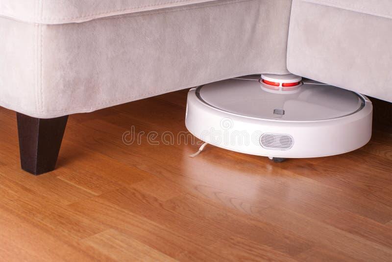 机器人吸尘器跑在沙发下在层压制品的地板现代聪明的清洁工艺家务的屋子里 库存图片