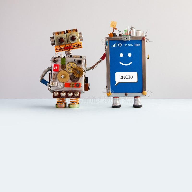 机器人和兴高采烈的流动多孔的小配件 在米黄灰色背景的机器人玩具字符 创造性的设计触摸屏 库存照片