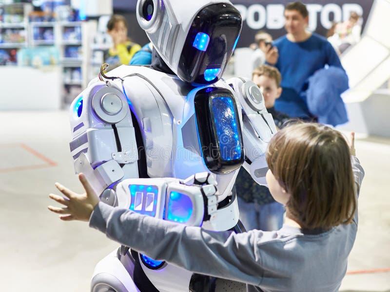 机器人机器人靠机械装置维持生命的人与一个小男孩沟通 库存照片