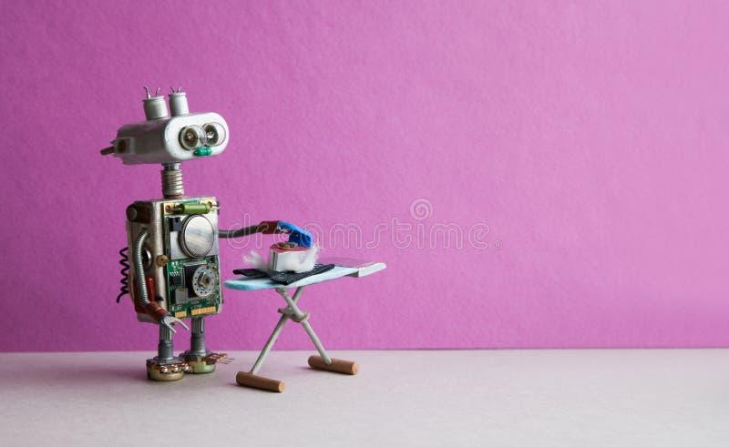 机器人电烙有铁的家事助理黑裤子在委员会 桃红色紫罗兰色墙壁灰色地板室内部 图库摄影