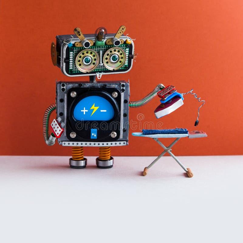 机器人电烙的服务概念 国内有铁的机器人家事助理电烙的蓝色牛仔裤在委员会 红色墙壁 免版税图库摄影