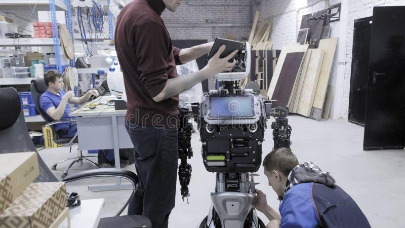 机器人的生产的工厂 两位工程师审查一个机器人 在实验室里创造一个新的机器人 连接 免版税库存照片