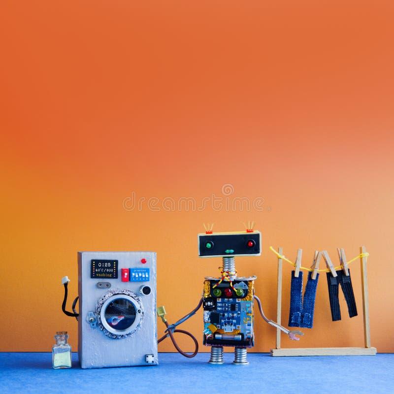 机器人自动化洗衣房模板 银色洗衣机,人` s牛仔裤裤子在与晒衣夹的晒衣绳烘干了 库存照片