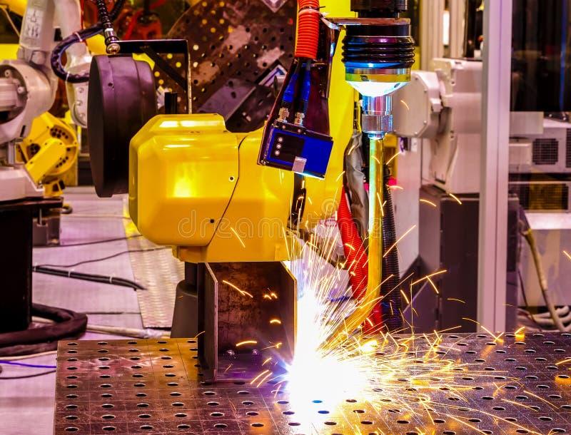 机器人蓝色和黄色火焰焊接特写镜头与浪花的在工厂 景深迷离 免版税库存照片