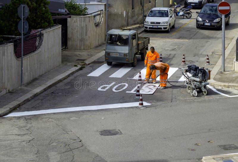 机器和工作者修路用途的路和交通标志绘画的 库存照片