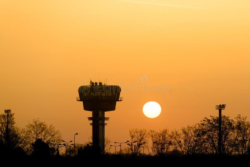 机场在日出的塔台剪影 免版税库存图片