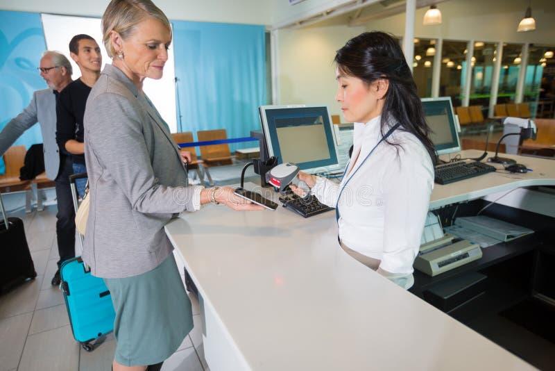 机场接待员在公共汽车举行的巧妙的电话的扫描条形码 免版税图库摄影
