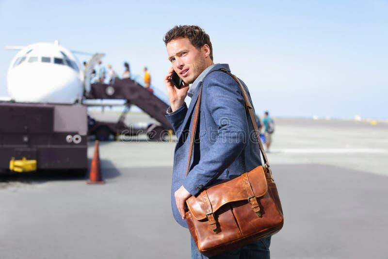 机场智能手机的商人乘飞机 免版税图库摄影