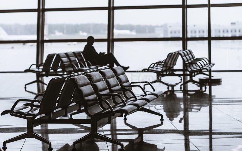 机场有坐的人剪影的离开大厅  免版税库存图片