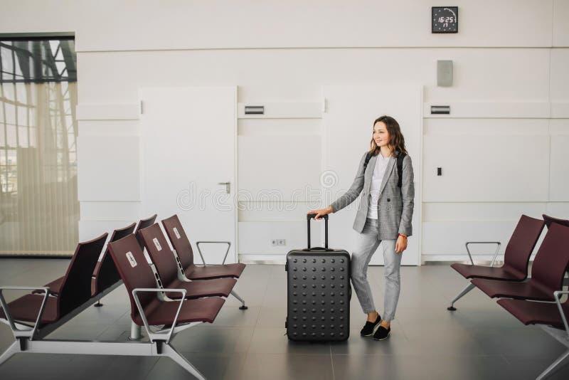 机场身分的女孩与她行李等待 免版税库存照片