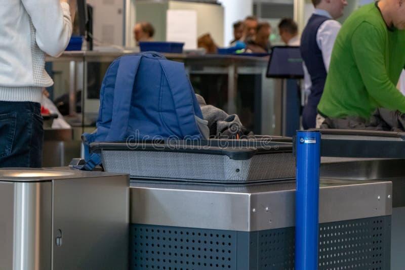 机场,慕尼黑,德国,4月2019 09日:在安检点的蓝色背包在机场 免版税库存图片