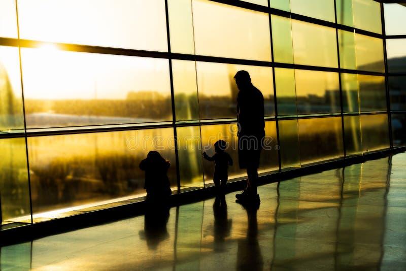 机场,父亲剪影有孩子的,在高窗口,都伯林爱尔兰,日出后的被弄脏的飞机 免版税库存照片