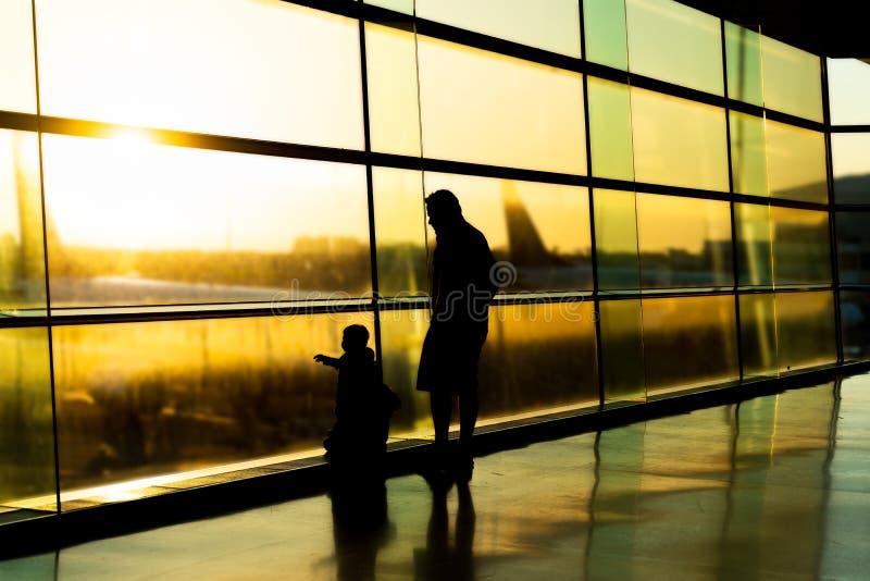 机场,等待他们的飞行,父亲,都伯林爱尔兰剪影的家庭有孩子的 免版税图库摄影