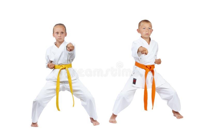 机架kiba dachi的孩子打拳打gyaku-tsuki 库存图片