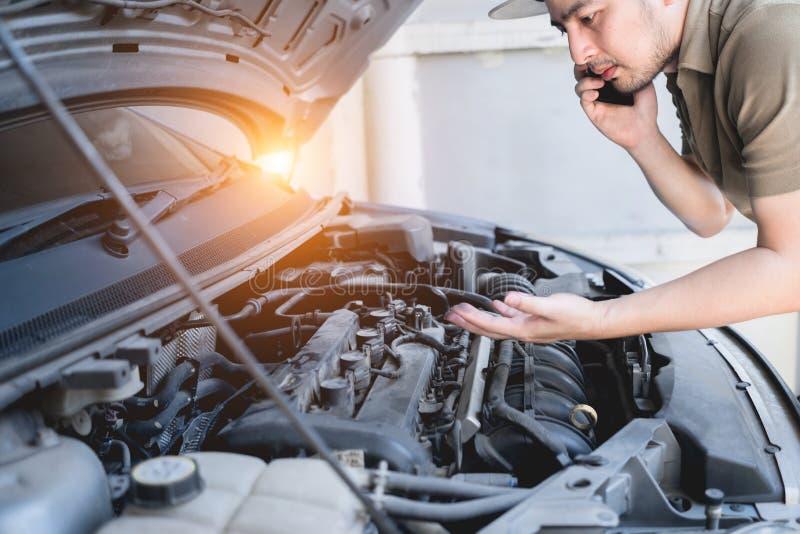 机械固定的汽车在家 由手机的修理公司忠告 技工,检查发动机的技术员人 汽车服务 免版税库存照片