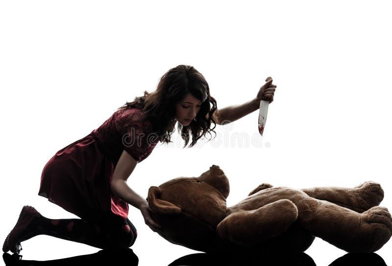 杀害她的玩具熊剪影的奇怪的少妇 免版税库存照片