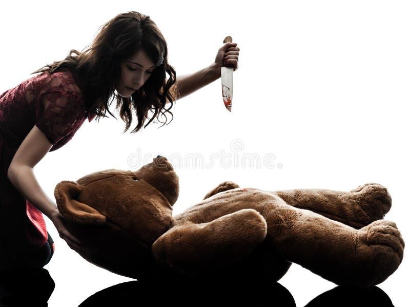 杀害她的玩具熊剪影的奇怪的少妇 库存图片