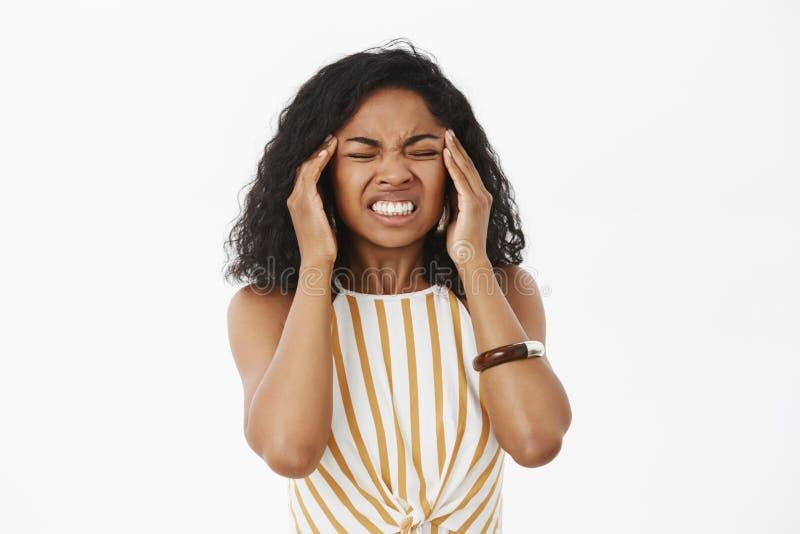 杀害我的偏头痛 握紧从痛苦的强烈的生气的年轻非裔美国人的女实业家画象牙 库存图片