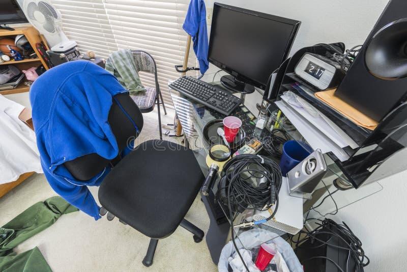 杂乱十几岁的男孩卧室书桌 免版税图库摄影