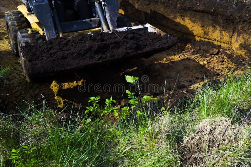 杂乱推土机播种的看法有土壤的在它的在挖掘工作期间的桶 库存图片