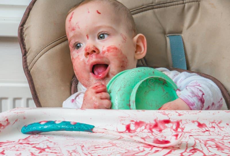 杂乱矮小的婴孩吃着从碗的晚餐 图库摄影