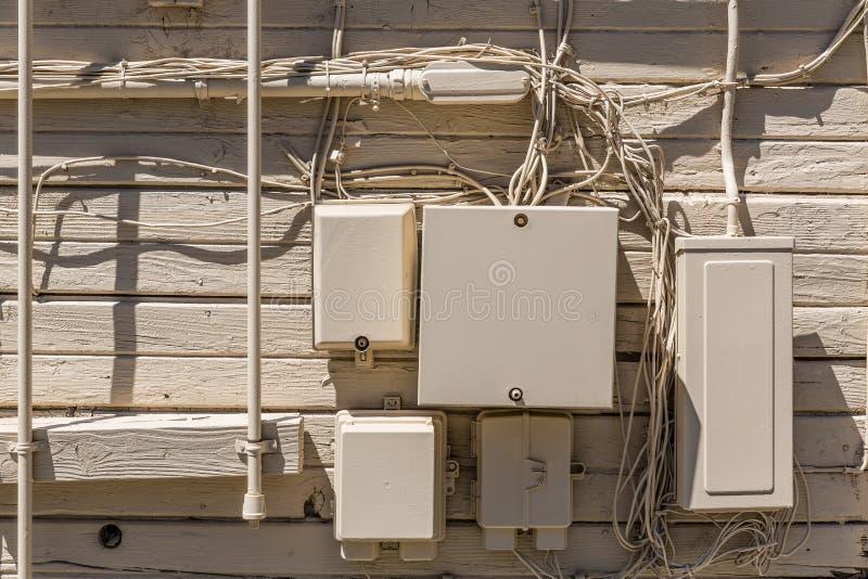 杂乱缆绳和电子箱子在木米黄墙壁 免版税库存图片