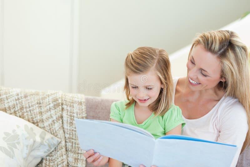 读杂志的母亲和女儿 库存图片