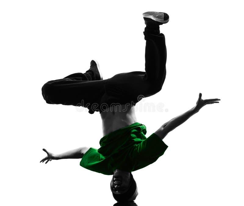 年轻杂技断裂舞蹈家breakdancing的人剪影 免版税库存照片
