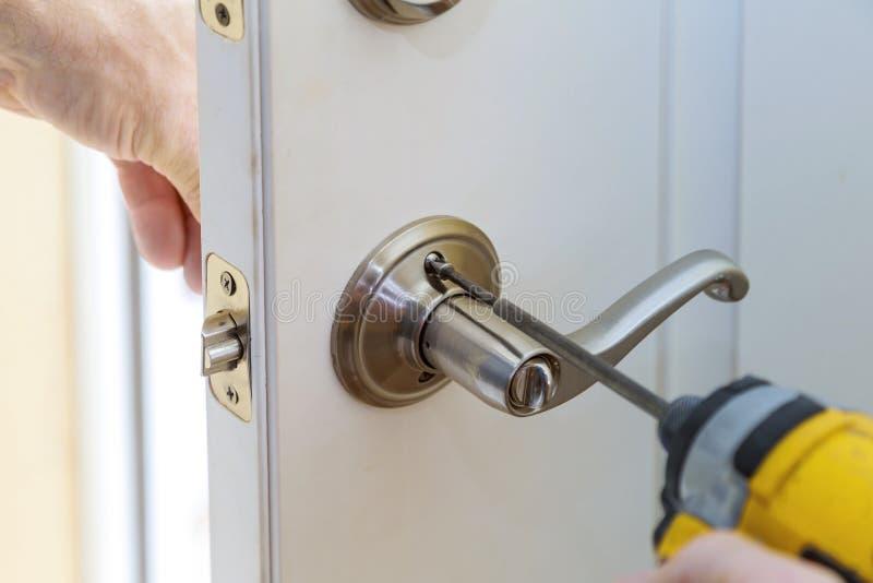 杂物工修理在worker& x27的门锁; 安装新的门衣物柜的s手 免版税图库摄影
