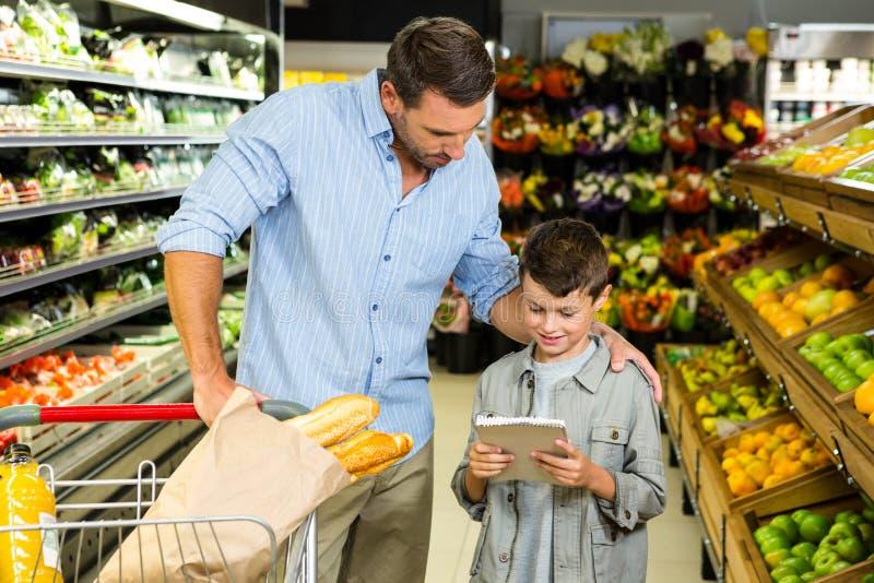 读杂货名单的父亲和儿子 免版税库存照片