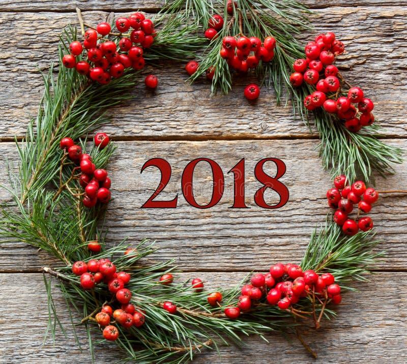 杉木分支和红色花揪圣诞节花圈在木背景 新年题字2018年 免版税库存图片