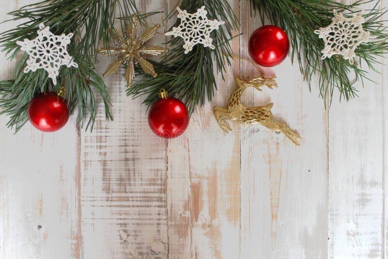 杉木分支,红色圣诞节球,在老白色背景钩编编织物的雪花 免版税图库摄影