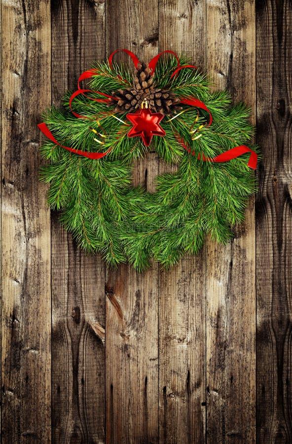 从杉木枝杈和红色球的圣诞节花圈在木头 图库摄影