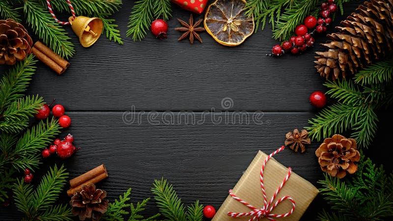 杉树分支和圣诞装饰在黑木背景与拷贝空间 图库摄影