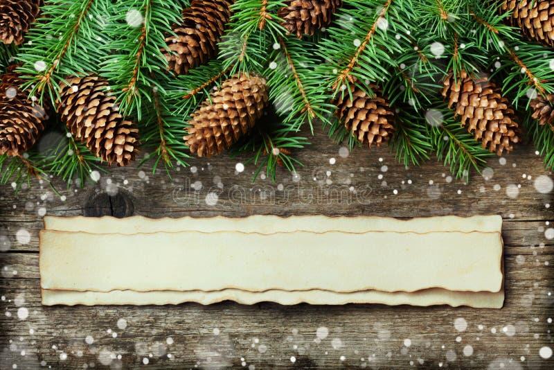杉树和针叶树锥体圣诞节背景在老葡萄酒木板,意想不到的雪作用和年迈的纸与拷贝spac 库存照片